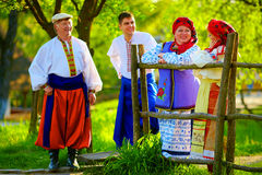 Happy ukrainian family in traditional costumes talking near the wooden fence Royalty Free Stock Images