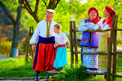 Happy ukrainian family in traditional costumes talking outdoor Stock Photography