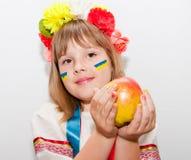 Happy ukrainian girl with apple. Happy teen ukrainian girl with hands near face and apple Royalty Free Stock Photography