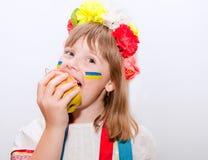 Happy ukrainian girl with apple. Happy teen ukrainian girl with hands near face and apple Royalty Free Stock Image