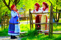 Happy ukrainian women, dressed in traditional costumes, talking on the street Stock Photo