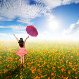 Happy umbrella woman jumping in flower garden and sun sky Royalty Free Stock Photos