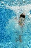 Happy underwater child jumps to swimming pool Stock Images