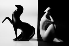 Happy and unhappy. Two simple smooth ceramic statues - black horse and white female - on black and white background, symbolizing contradiction and opposites Royalty Free Stock Image