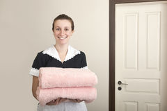 Happy uniformed maid with towels Royalty Free Stock Photo