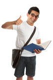 Happy university college student thumbs up. An excited happy university or college student, holding a text book and with thumbs up approval success, hand sign Stock Photos