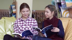 Happy university girls enjoying reading in library stock video