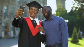 Happy university student graduation mantle and father taking selfie smartphone