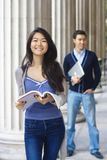 Happy university students. With columns at the background Royalty Free Stock Photo
