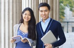 Happy university students outdoors. Happy university students with columns at the background Royalty Free Stock Photo
