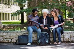 Happy University Students Using Digital Tablet On. Professor helping students on campus using digital tablet Stock Image