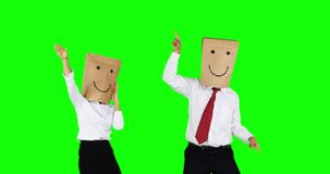 Happy unknown business people dancing together. Two happy unknown business people with paper bag on their head, celebrating their success by dancing together