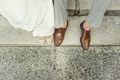 Happy unrecognized wedding couple in love feet casual shoes. Happy unrecognized wedding couple in love feet shoes.Legs bridal grooms wearing shoes.Men in casual Royalty Free Stock Image
