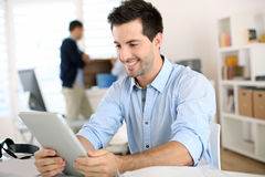 Happy unshaven man holding tablet in office Stock Photo