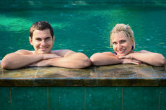 Happy vacation in swimming pool. Happy smiling young couple relaxing in a swimming pool on a poolside in tropical resort Stock Image