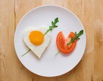 Happy Valentine Day!. Fried egg and slice of tomato in the shape of two hearts pierced with two arrows Stock Photos
