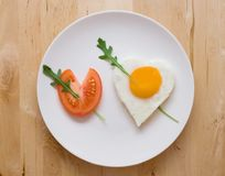 Happy Valentine Day!. Fried egg and slice of tomato in the shape of two hearts pierced with two arrows Royalty Free Stock Images