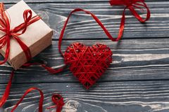 Happy valentine day card concept. stylish red present and heart. Ribbons on black rustic wooden background. greeting flat lay with space for text Stock Image