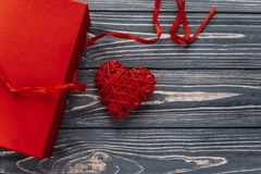 Happy valentine day card concept. stylish red present and heart. Ribbons on black rustic wooden background. greeting flat lay with space for text Stock Photos