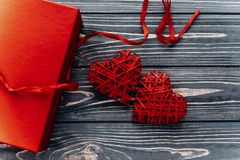Happy valentine day card concept. stylish red present and heart. Ribbons on black rustic wooden background. greeting flat lay with space for text Stock Images