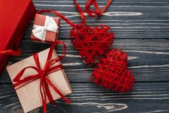 Happy valentine day card concept. stylish red present and two  h. Eart ribbons on black rustic wooden background. greeting flat lay with space for text Stock Photo