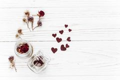 Happy valentine day. stylish hearts in glass jar and roses flat. Lay on white wooden background. unusual card. greeting card with space for text. wedding or stock photo