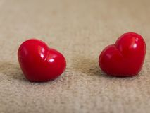 Happy valentine day two red hearts on carpet light brown Stock Photos