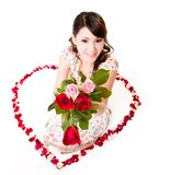 Happy valentine girl with roses. Young woman with roses sitting inside a rose petal heart shape Royalty Free Stock Image