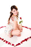 Happy valentine girl with roses. Young woman with roses sitting inside a rose petal heart shape Royalty Free Stock Images