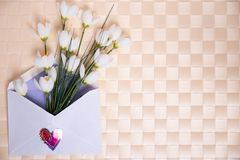 Happy Valentine or Mothers Day background. Beautiful bouquet of white flowers in an open envelope with a hearts symbol lying on a stock image