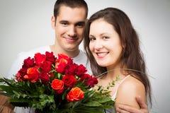 Happy Valentine`s Couple Holding Bouquet Of Roses. Studio shot of happy valentine`s couple holding bouquet of roses Stock Photo