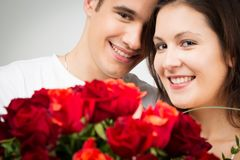 Happy Valentine`s Couple Holding Bouquet Of Roses. Studio shot of happy valentine`s couple holding bouquet of roses Royalty Free Stock Images