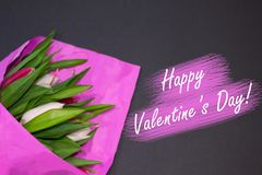 Happy Valentine`s Day. Bouquet of fresh tulip buttons in pink paper on black background. Pink and white flowers lie on table in stock photography