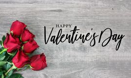 Happy Valentine`s Day Calligraphy Font Text with Beautiful Red Rose Flowers in Corner Over Light Wood Background