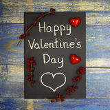 Happy Valentine`s Day card decorated with red hearts and wild rose fruits Royalty Free Stock Photos