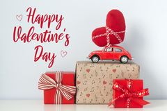 Happy Valentine`s Day card. Red retro toy car with plush heart.  royalty free stock photography