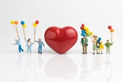 Happy Valentine`s day card or wallpaper concept, miniature peopl. E happy love family holding balloons with red heart shape on white background Stock Photo