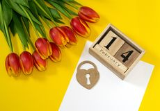 Happy Valentine`s Day concept. Bouquet of red button tulips, wooden calendar with 14 february, heart and white sheet of paper on royalty free stock photography