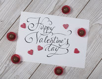 Happy Valentine`s day concept with praline and glitteresd hearts. Happy Valentine`s day concept card with praline and glittered hearts on white wood royalty free stock images