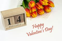 Happy Valentine`s day!14 february composition with bouquet of red tulips and wooden calendar. Concept of love, gift, tenderness, stock image