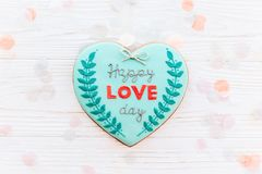 Happy valentine`s day greeting card. happy love day text on cook. Ie heart on white rustic wooden background with confetti flat lay. space for text . mock-up Royalty Free Stock Photography