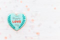 Happy valentine`s day greeting card. happy love day text on cook. Ie heart on white rustic wooden background with confetti flat lay. space for text . mock-up Royalty Free Stock Image