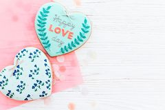 Happy valentine`s day greeting card. happy love day text on cook. Ie heart and flowers on white rustic wooden background with confetti flat lay. space for text Stock Photography