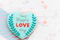 Happy valentine`s day greeting card. happy love day text on cook. Ie heart on white rustic wooden background with confetti flat lay. space for text . mock-up Royalty Free Stock Images