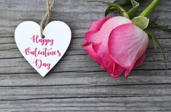 Happy Valentine`s Day greeting card with pink rose and decorative white heart with text on old wooden background.14th of February. stock photography