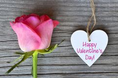Happy Valentine`s Day greeting card with pink rose and decorative white heart with text on old wooden background.14th of February. stock images
