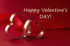 Happy Valentine's Day Greeting card. Two red heart shaped cookie cutters on beautiful red background. Happy Valentine's Day inscription. Greeting card royalty free stock images