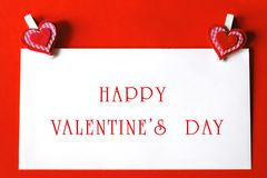 Happy Valentine's Day - paper sheet with heart shaped clips Royalty Free Stock Images