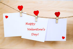 Happy Valentine`s Day on stickers hanging on heart shape pins. Happy Valentine`s Day text written at paper stickers hanging on red heart shape wooden pins and royalty free stock photo