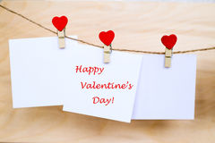 Happy Valentine`s Day on stickers hanging on heart shape pins. Happy Valentine`s Day text written at paper stickers hanging on red heart shape wooden pins and royalty free stock images